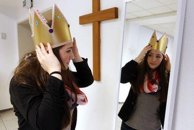 Die Sternsingerin Jana probiert ihre Krone vor einem Spiegel an. So kann sie sehen ob die Krone gut aussieht und gut auf dem Kopf sitzt.