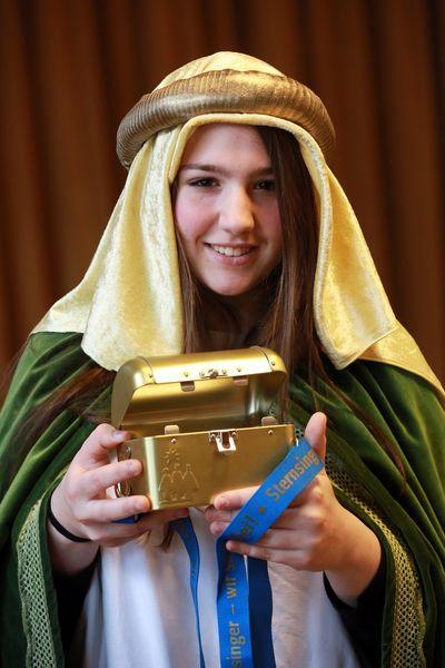 Eine Sternsingerin in einem grünen Umhang mit goldenen Verzierungen an den Ärmeln hält mit beiden Händen eine Sternsinger Spendenbox. Die Spendenbox ist golden und hat auch ein Schloss um die Box sicher zu verschließen.
