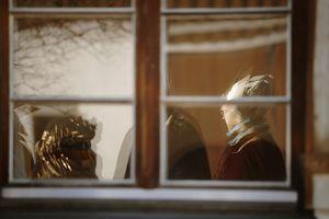 Ein Blick von draußen durch ein geschlossenes Fenster in ein Wohnzimmer hinein.  Die Sternsinger stehen in dem Zimmer und sind in warmes Licht getaucht.