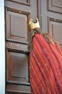 Eine Sternsingerin in einem dunkel rot und hell rot gestreiftem Umhang, schreit den Segen der Sternsinger an die Tür des Schlosses Bellevue.