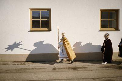 Eine Gruppe von Sternsinger auf dem Weg zur nächsten Station. Sie tragen den Stern vor sich her. Die Sonne wirft die Schatten der Drei an eine Hauswand.