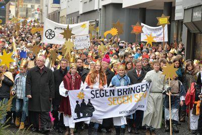 Sternsingerzug mit 2.500 Sternsingern zieht durch die Paderborner Innenstadt. Die Straße auf der normalerweise die Autos fahren ist voller Menschen in Gewändern und Kronen.