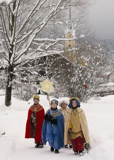 Vier Sternsinger auf ihrem Weg durch das verschneite Dorf. Die Äste an den Bäumen sind dick von Schnee bedeckt genau so wie die umliegenden Häuser. Die Sternsinger  tragen rote, blaue und beige Umhänge und ahn auch die Kronen auf dem Kopf. Zudem tragen sie den Stern der Sternsinger an einem langen Stock mit sich.