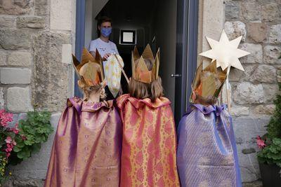 Sternsinger stehen an der Haustür und halten einen selbstgebastelten Sternsinger-Kescher in der Hand, mit dem sie kontaktlos Geld sammeln können.