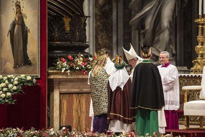 Drei Sternsinger stehen vor Papst Franziskus. Sie haben die traditionellen Gewänder an. Die Sternsinger haben an der Gabenprozession teilgenommen. Sie stehen direkt vor dem Papst.
