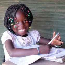 Ines sitzt an einer Schulbank und hat viele Hefte auf dem Tisch. Sie guckt mit einem breiten Grinsen in die Kamera.