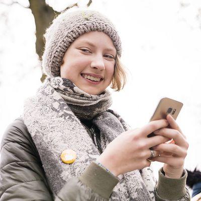 Sternsinger-Begleiterin lächelt mit Handy in der Hand in die Kamera.
